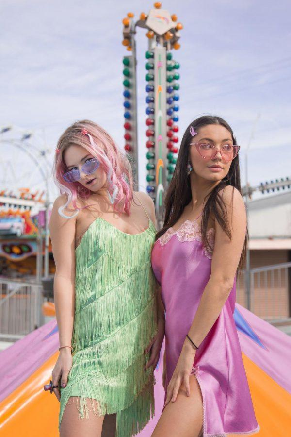 Models Natalie Cornejo and Emma Bowder pose together in colorful slip dresses and transparent colorful sunglasses.